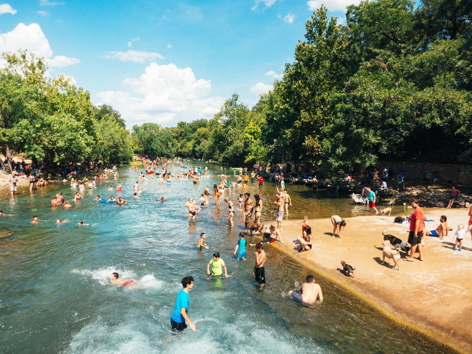 Many families and groups playing in crowded river_austin texas_best corporate retreat destinations_flok