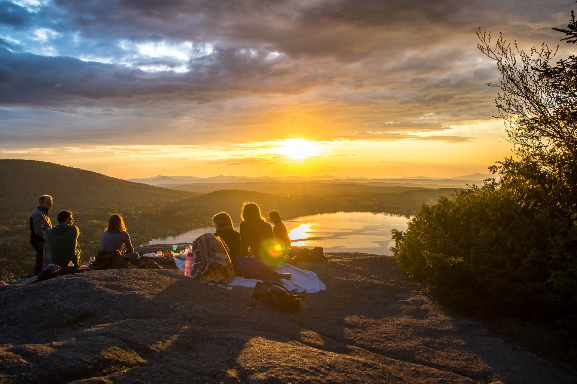group on top of a mountain watching the sun set_how to plan a corporate retreat_flok
