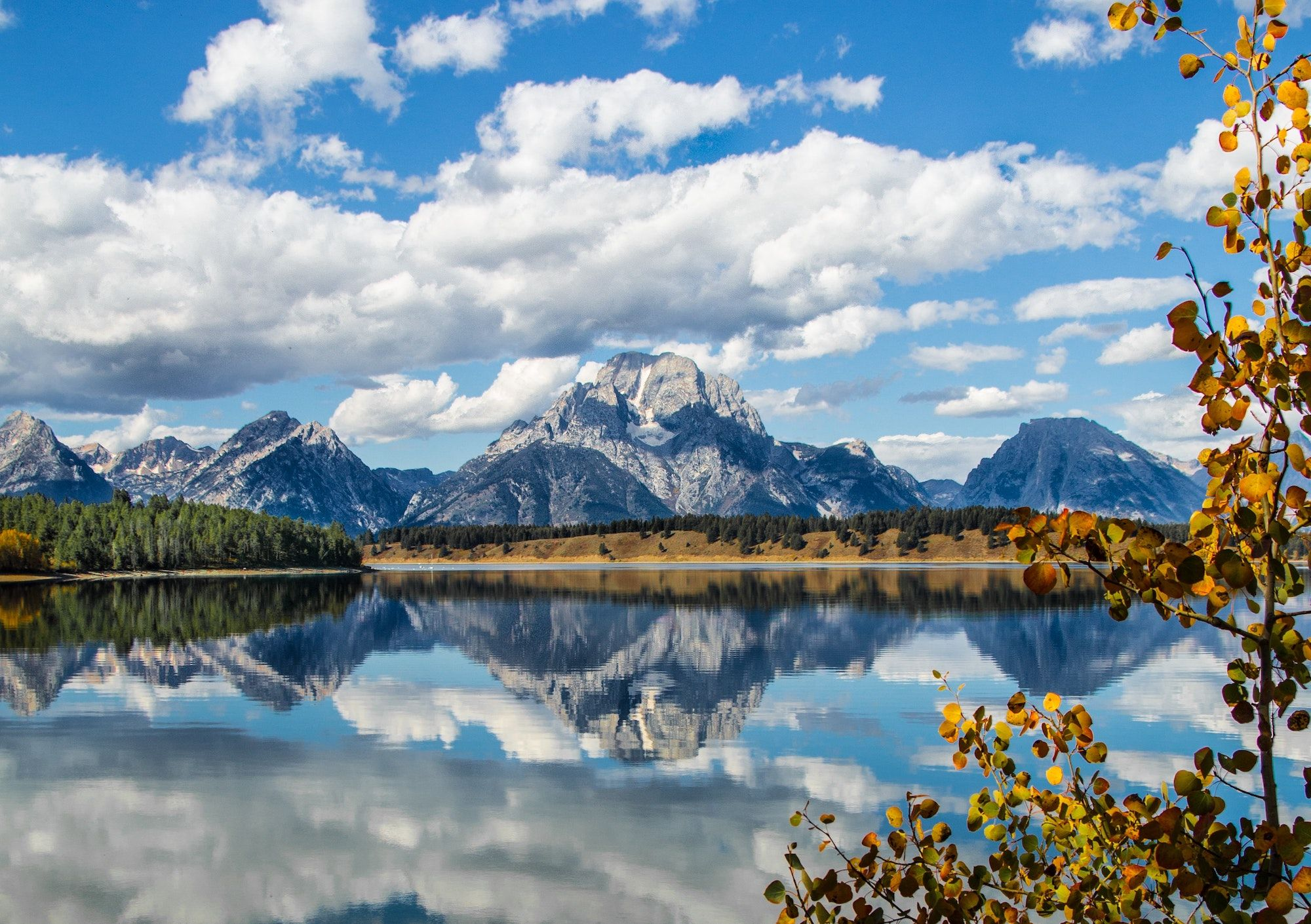 mountain surrounded by clouds reflecting off of lake in foreground_best corporate retreat destinations_flok