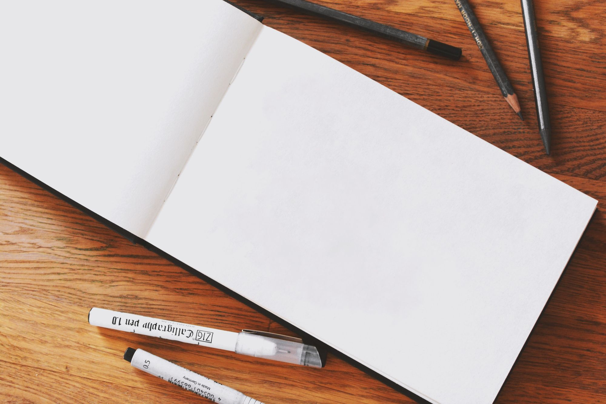 Blank notebook surrounded by pencils and markers_team building activities for work_flok